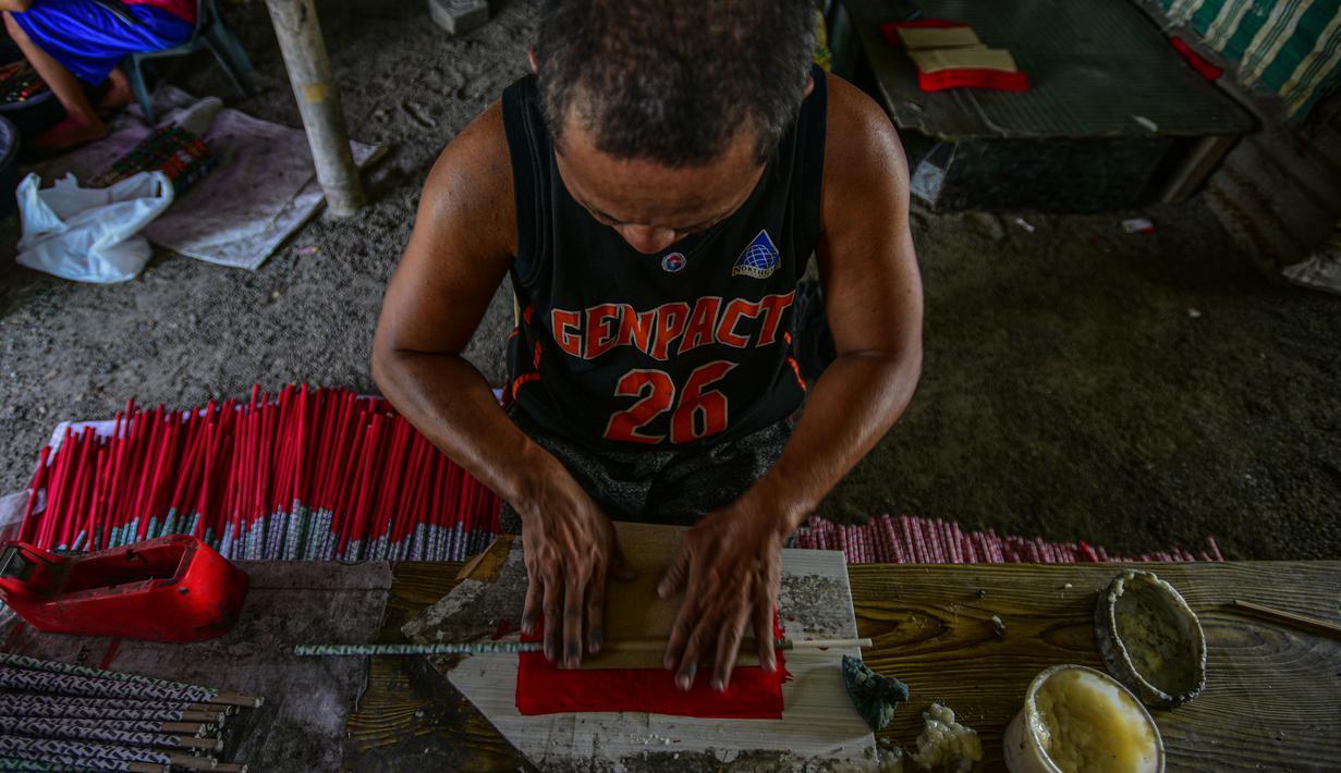 Pekerja menyelesaikan pembuatan petasan di sebuah pabrik di Bocaue, Bulacan, Filipina, Jumat (27/12/2019). Petasan-petasan tersebut akan dijual untuk perayaan Tahun Baru 2020. (Maria TAN/AFP)