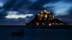Kastil Mont Saint-Michel terlihat saat malam hari di Normandia, Prancis barat laut (31/8/2019). Mont Saint-Michel yang berjuluk 'Wonder of the West' bertengger di pulau berbatu di tengah gumuk pasir antara Normandia dan Brittany. (AFP Photo/Joel Saget)