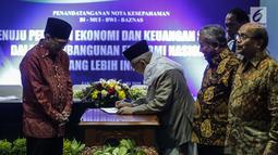 Ketua Umum MUI Ma'ruf Amin menandatangani nota kesepahaman (Mou) dengan BI, Baznas, dan BWI di Gedung MUI, Jakarta, Rabu (24/1). MoU terkait peranan ekonomi dan keuangan syariah dalam pembangunan nasional yang lebih inklusif. (Liputan6.com/Faizal Fanani)