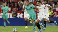 Gelandang Real Madrid, Eden Hazard menggiring bola dari kejaran pemain Sevilla, Daniel Carrico pada pertandingan lanjutan La Liga Spanyol di stadion Ramon Sanchez Pizjuan di Seville (22/9/2019). Real Madrid menang tipis atas Sevilla 1-0. (AP Photo/Miguel Morenatti)