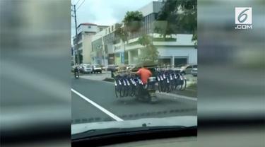 Seorang pria mengendarai motor sambil membawa 16 sepeda di China. Sepeda itu ia angkut menggunakan kayu yang diletakkan pada bahunya.