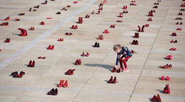 Seorang anak di antara instalasi ratusan sepatu merah untuk memprotes kekerasan terhadap perempuan di Habima Square, Tel Aviv, Selasa (4/12). Sepanjang tahun ini, 24 perempuan Israel tewas akibat tindakan kekerasan dalam rumah tangga. (AP/Oded Balilty)