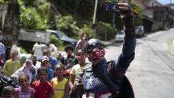 Polisi militer Everaldo Pinto, berkostum Captain America, berfoto dengan anak-anak di tengah pandemi COVID-19 di Petropolis, Rio de Janeiro, Brasil, Kamis (15/4/2021). Dalam aksinya, Pinto membagikan kotak berisi produk pembersih dan masker untuk mencegah paparan corona. (AP Photo/Silvia Izquierdo)