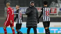 Manajer tim Liverpool, Jurgen Klopp menghampiri bek Newcastle United, Jamal Lewis untuk berjabat tangan usai berakhirnya laga lanjutan Liga Inggris 2020/21 pekan ke-16 di St James' Park, Rabu (30/12/2020). Liverpool bermain imbang 0-0 dengan Newcastle United. (AFP/Scott Heppell/Pool)