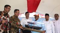 General Manajer Divisi Bisnis Usaha Kecil 2 BNI Bambang Setyatmojo (kedua kiri) menyerahkan miniatur Kapal Latih Nelayan berukuran 5 GT kepada perwakilan nelayan di Desa Ciwaru, Kecamatan Ciemas, Kabupaten Sukabumi, Jawa Barat, Sabtu (20 Juli 2019).