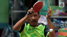 Petenis mengembalikan bola ke lawannya saat kejuaraan Bintikers Cup Tenis Meja di Pasar Grogol, Jakarta, Sabtu (14/12/2019). Turnamen Bintikers Cup Tenis Meja diikuti 125 orang yang merupakan perwakilan pedagang pasar se-Jabodetak dan luar Jakarta seperti Surabaya. (merdeka.com/Imam Buhori)