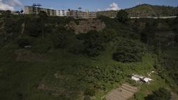 Eulices Cortez menyiapkan sebidang tanah untuk menanam kacang di lingkungan La Dolorita di Caracas, Venezuela (13/9/2020). Hasil panen dijual untuk mengatasi situasi keuangan mereka karena krisis ekonomi yang meningkat yang diperparah oleh pandemi virus corona. (AP Photo/Matias Delacroix)