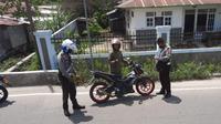 Anggota Satuan Lalu Lintas Polres Gorontalo Kota saat melakukan penilangan terhadap pengguna knalpot bising (Arfandi Ibrahim/Liputan6.com)