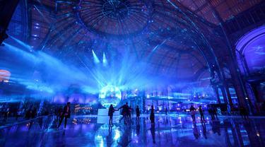 Orang-orang berseluncur di arena ice skating di bawah kubah kaca mewah legendaris, Grand Palais, Paris, Selasa (17/12/2019). Aren seluncur es musiman ini terbuka untuk umum selama liburan Natal. (Photo by Thomas SAMSON / AFP)