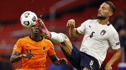 Bek Italia, Danilo D'Ambrosio, berebut bola dengan penyerang Belanda, Quincy Promes, pada laga UEFA Nations League di Amsterdam Arena, Selasa (8/9/2020) dini hari WIB. Italia menang tipis 1-0 atas Belanda. (AFP/Maurice Van Steen/ANP)