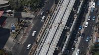 Kendaraan melintas di bawah proyek pembangunan Light Rail Transit (LRT) Jabodebek di Rasuna Said, Kuningan, Jakarta, Rabu (21/8/2019). Jadwal pengoperasian LRT Jabodebek molor dari target yang pada awalnya direncanakan bisa beroperasi pada 2019. (Liputan6.com/Angga Yuniar)