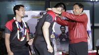 Ketua Umum PBSI, Wiranto, mengalungkan bunga kepada Hendra Setiawan disaksikan oleh rekannya, Mohammad Ahsan, saat disambut di Bandar Udara Soekarno-Hatta, Cengkareng, Selasa (27/8/2019). Ahsan/Hendra disambut usai menjadi juara di Kejuaraan Dunia 2019. (Bola.com/Yoppy Renato)