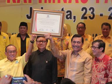 Ketua umum Partai Golkar, Aburizal Bakrie dengan Menkopolhukam Luhut Panjaitan mengangkat pigura berisi hasil keputusan Rapimnas Partai Golkar 2016, Jakarta, Senin (25/1/2016). (Liputan6.com/Angga Yuniar)