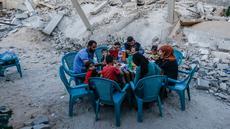 Sebuah keluarga Palestina berbuka puasa di sebelah rumah mereka yang hancur selama eskalasi dua hari, di Rafah, Jalur Gaza selatan (8/5/2019). Perang yang terjadi antara Gaza dan Israel masih berlangsung hingga detik ini. (AFP Photo/Said Khatib)
