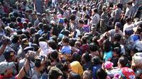 Petugas kepolisian berusaha menenangkan warga yang saling dorong saat pembagian zakat di PT Gudang Garam, Kediri, Jatim. (Antara)