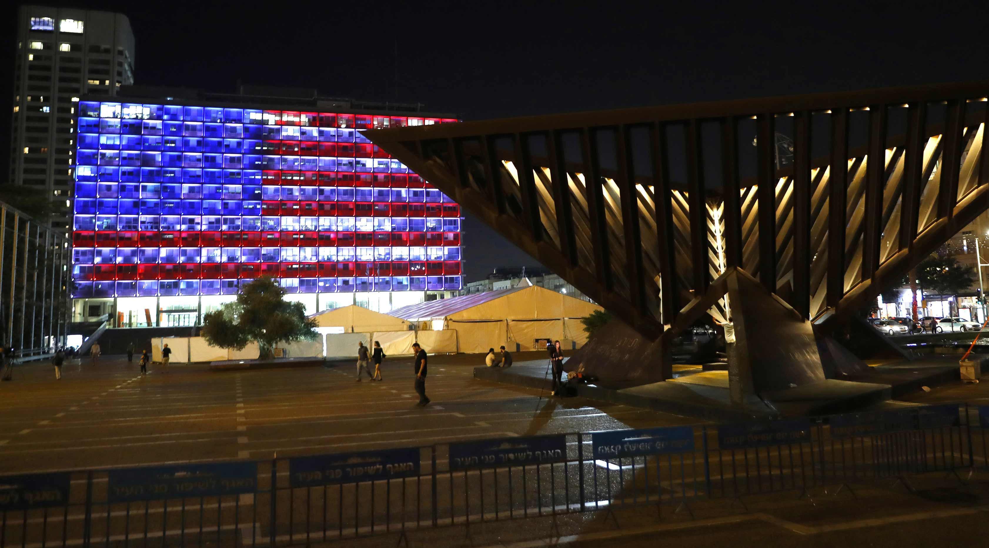 Suasana di dekat balai kota Tel Aviv yang dihiasi warna bendera AS untuk menghormati korban penembakan brutal di Las Vegas di Rabin Square, Tel Aviv (2/10). Menurut laporan, pelaku Stephen Paddock bunuh diri di lokasi kejadian. (AFP Photo/Jack Guez)