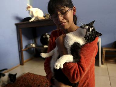 Lizi Inga saat memegang seekor kucing dirumahnya, Lima, Peru (4/8/2015). Inga merupakan seorang wanita yang mempunyai penampungan kucing sekitar 50 ekor dirumahnya sendiri. (Reuters/Mariana Bazo)