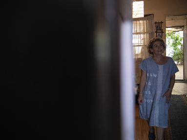 Pia Ortiz yang berusia 60 tahun berpose di rumahnya di komune Central Station Santiago, Chile pada 2 Maret 2021. Pia Ortiz yang kehilangan pekerjaannya karena pandemi COVID-19, sekarang menjahit pakaian dari celana jeans tua untuk jual di pasar. (Martin BERNETTI / AFP)