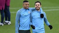 Pemain Manchester City, Gabriel Jesus merangkul Bernardo Silva saat sesi latihan jelang laga Liga Champions di Manchester, Selasa (6/3/2018). Manchester City akan berhadapan dengan FC Basel. (AFP/ Oli Scarff)