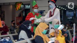 Petugas KAI yang mengenakan kostum Natal membagikan masker kepada calon penumpang di Stasiun Senen, Jakarta, Jumat (25/12/2020). Pembagian ini juga untuk memutus mata rantai penyebaran COVID-19 saat mudik Natal dan Tahun Baru 2021. (merdeka.com/Imam Buhori)