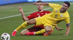 Penyerang Ukraina, Roman Yaremchuk, berebut bola dengan bek Swiss, Nico Elvedi, pada laga Nations League di Stadion Arena Lviv, Jumat (4/9/2020) dini hari WIB. Ukraina menang 2-1 atas Swiss. (AFP/Anatolii Stepanov)