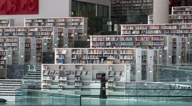 Seorang wanita melihat-lihat koleksi buku di Perpustakaan Nasional Qatar di ibu kota Doha pada 19 Mei 2019. Bangunan megah karya arsitek Rem Koolhaas ini memiliki luas 45 ribu meter persegi. (KARIM JAAFAR / AFP)