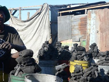 """Seorang penjual arang menunjukan dagangannya di pasar sentral Les Cayes, Haiti, (25/1). Menteri Lingkungan Hidup Haiti akan membuat peraturan jaringan """"hutan energi"""" yang menghasilkan kayu untuk arang dan kayu bakar. (AP/David McFadden)"""