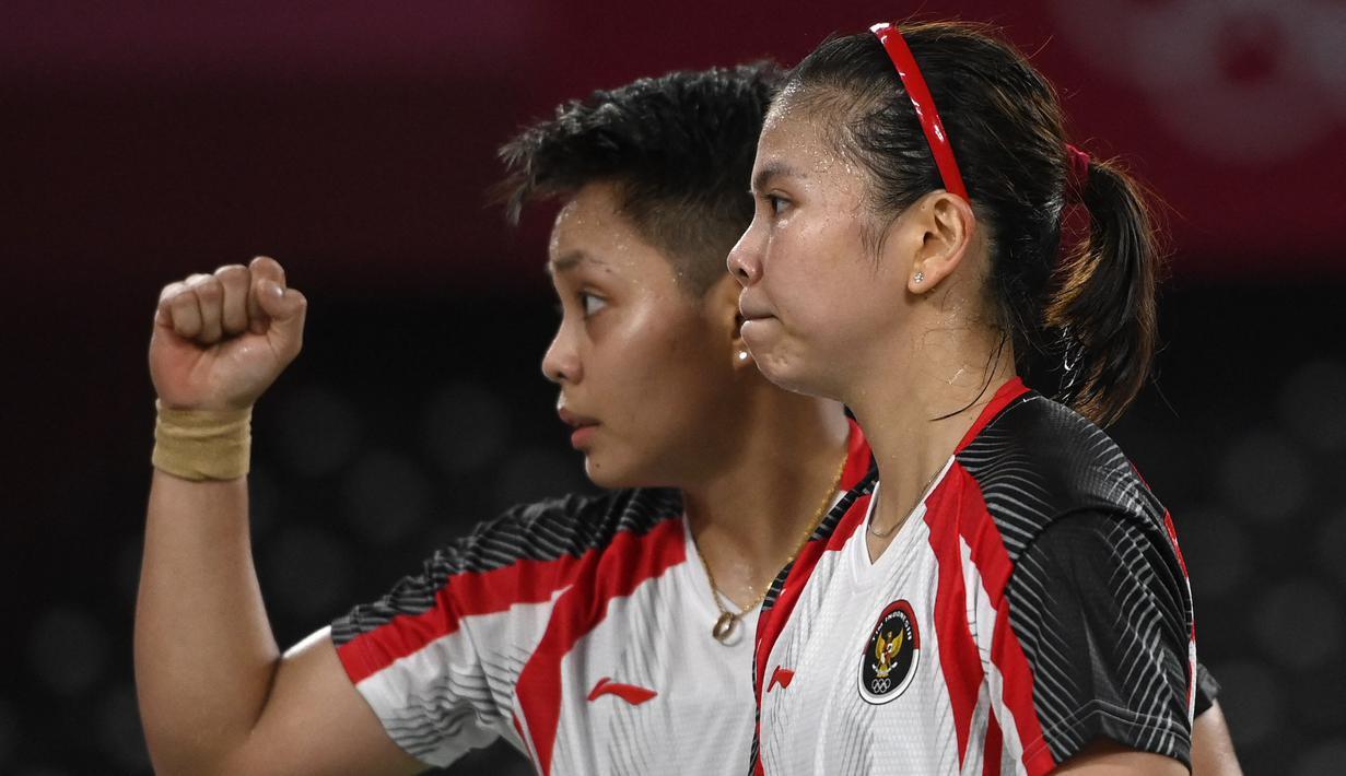 Reaksi ganda putri Indonesia Apriyani Rahayu (kanan) dan Greysia Polii usai menang atas pasangan nomor satu dunia asal Jepang Yuki Fukushima dan Sayaka Hirota pada penyisihan Grup A cabang bulu tangkis Olimpiade Tokyo 2020 di Musashino Forest Sports Plaza, Selasa (27/7/2021). (Alexander NEMENOV/AFP)