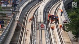 Pekerja menyelesaikan pembangunan LRT (Light Right Transit) Jabodebek di kawasan Kampung Makasar, Jakarta, Sabtu (26/10/2019). LRT akan diuji coba pada awal November 2019. (Liputan6.com/JohanTallo)