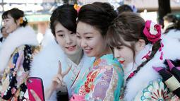 Tiga wanita berpakaian Kimono swafoto selama upacara perayaan Coming of Age Day atau Hari Kedewasaan di Tokyo  (14/1). Upacara kedewasaan sudah digelar di Jepang untuk pangeran muda sejak 714 Masehi. (AP Photo/Koji Sasahara)