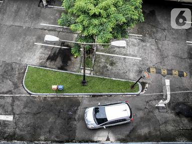 Sebuah mobil melintas di lahan parkir yang sepi di sebuah gedung, Jakarta, Kamis (1/5/2020). Indonesia Parking Association (IPA) menyatakan terjadi penurunan bisnis parkir sebesar 75-90 persen seiring penerapan PSBB untuk mencegah penyebaran COVID-19 di Jabodetabek. (Liputan6.com/Faizal Fanani)