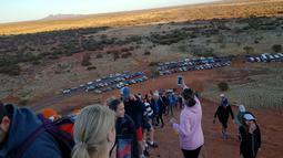 Selebaran yang diterima pada 10 Oktober 2019 memperlihatkan para wisatawan mendaki Uluru di Utara Australia.  Para pengunjung yang mengetahui rencana penutupan situs gunung batu ikonik tersebut langsung menyerbu Uluru untuk kemah dan mendaki sebelum larangan resmi diterapkan. (HO/ @koki_mel_aus/AFP)