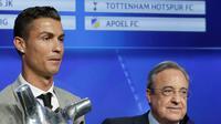 Cristiano Ronaldo memegang piala Penyerang Terbaik Liga Champions dan Pemain Terbaik UEFA 2016/17 berfoto bersama presiden Real Madrid Florentino Perez di Grimaldi Forum, Monaco (24/8). (AP Photo/Claude Paris)