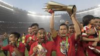 Kapten Persija Jakarta, Ismed Sofyan, mengangkat piala bersama rekan-rekannya usai mengalahkan Mitra Kukar pada laga Liga 1 di SUGBK, Jakarta, Minggu (9/12). Persija menang 2-1 atas Mitra. (Bola.com/Vitalis Yogi Trisna)