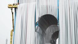 Pekerja membungkus monumen Arc de Triomphe di Paris, pada Selasa (14/9/2021).  Arc de Triomphe yang dikenal sebagai salah satu bangunan ikonik di Paris tersebut dibungkus kain polypropylene daur ulang seluas 25.000 meter persegi berwarna biru keperakan. (AP Photo/Thibault Camus)