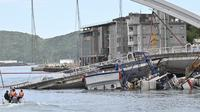 Tim penyelamat menggunakan kapal kecil bersiap mengevakuasi dalam pekerjaan kapal di lokasi jembatan yang ambruk di pelabuhan Nanfangao di kota Suao (1/10/2019). Tiga perahu nelayan yang tertimpa serta kendaraan di atas jembatan yang rusak, termasuk truk tangki. (AFP Photo/Sam Yeh)
