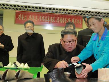 Pemimpin Korea Utara, Kim Jong-Un dibantu pekerja mengelem sepatu saat mengunjungi pabrik sepatu Wonsan, Korea Utara (3/12). (Photo by KCNA VIA KNS / various sources / AFP)