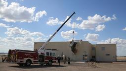 Proses evakuasi pesawat bermesin tunggal yang menabrak gedung di Bandara Regional Ak-Chin, Maricopa, Arizona, Amerika Serikat, Selasa (10/9/2019). Kecelakaan menyebabkan dua orang terluka. (AP Photo/Ross D. Franklin)