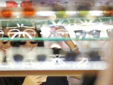 Dua wanita mencoba kaca mata di salah satu stand bazar dalam acara Fimela Fest 2018, Jakarta, Jumat (16/11). Fimela Fest 2018 diselenggarakan mulai tanggal 13-18 November 2018 di Gandaria City Mall, Jakarta. (Fimela.com/Bambang Ekoros Purnama)