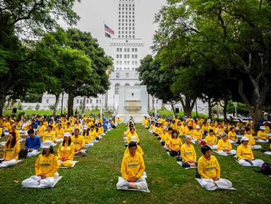 Sekelompok orang melakukan meditasi Falun Gong sebelum demonstrasi menentang pemerintah China, di luar Balaikota Los Angeles, California, Kamis (15/10). Presiden China Xi Jinping akan melakukan kunjungan kenegaraan di Washington. (REUTERS/Lucy Nicholson)