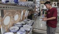 Pembeli melihat produk keramik yang dijual di kios kerajinan keramik kawasan Tanjung Priuk, Jakarta Utara, Kamis (23/9/2021). Pedagang mengaku pasokan keramik menurun hingga 70 persen seiring dangan pembatasan produksi pabrik akibat perpanjangan PPKM. (Liputan6.com/Herman Zakharia)