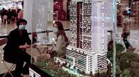 Agen real estat mempromosikan bangunan apartemen bertingkat tinggi di pusat perbelanjaan di Penang (1/8/2020). Malaysia tengah memperingatkan gelombang kedua virus corona COVID-19. (AFP Photo/Goh Chai Hin)