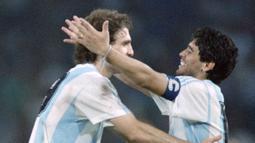 Penyerang Argentina, Diego Maradona, bersama Oscar Ruggeri merayakan kemenangan atas Italia pada laga semifinal Piala Dunia di Naples, Italia (3/7/1990). (AFP/Patrick Hertzog)
