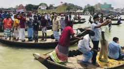 Warga menyaksikan proses evakuasi korban kecelakaan kapal feri di Sungai Buriganga, Dhaka, Bangladesh, Senin (29/6/2020). Kapal feri yang tenggelam mengangkut hingga 60 penumpang. (AP Photo/Al-emrun Garjon)