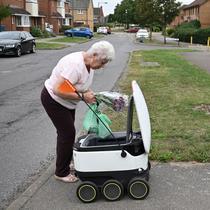 Sheila (71) mengambil kiriman dari robot otonom bernama Starship yang mengantarkan bahan makanan dari supermarket Co-op di Milton Keynes, Inggris, 20 September 2021. Robot Starship bertugas mengantarkan belanja dan makanan. (DANIEL LEAL-OLIVAS/AFP)