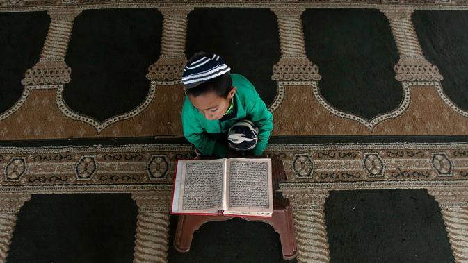 Seorang anak laki-laki membaca Alquran di sebuah masjid di Kabul, Afghanistan, Senin, (21/5). Anak-anak Afghanistan lebih memperdalam Alquran di saat Ramadan. (AP Photo/Rahmat Gul)