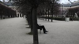 Seorang pria duduk di taman Royal Palais di Paris (22/3/2021).Sementara pemerintah Prancis bersikeras bahwa aturan tersebut tidak akan seketat di masa lalu, tindakan tersebut dikritik karena dianggap berantakan. (AP Photo/Lewis Joly)