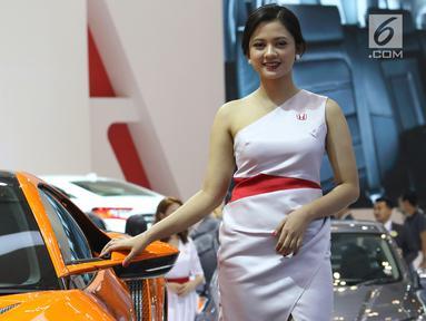 Model berpose di samping mobil yang dipamerkan pada Gaikindo Indonesia International Auto Show (GIIAS) 2019 di ICE BSD, Tangerang, Sabtu (20/7/2019). Kehadiran SPG atau model itu untuk menarik pengunjung serta memberikan informasi terkait produk otomotif yang ditawarkan. (Liputan6.com/Angga Yuniar)