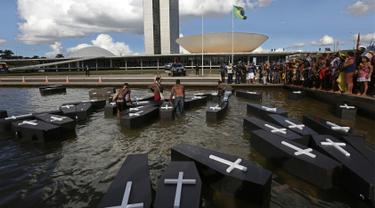 Sejumlah orang menceburkan replika peti mati saat menggelar aksi protes di luar gedung Kongres Nasional di Brasilia, Brasil (25/4). Mereka menuntut pertanggung jawaban atas terbunuhnya orang Indian karena masalah demarkasi lahan. (AP Photo/Eraldo Peres)