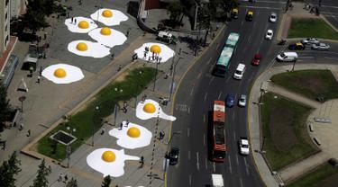 Telur ceplok raksasa berhamburan di jalanan Kota Santiago, Chile, 8 November 2016. Telur mata sapi raksasa ini merupakan bagian dari festival seni Hecho en Casa. (REUTERS / Pablo Sanhueza)